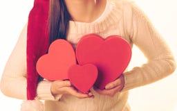 A menina guarda caixas de presente dadas forma coração Fotos de Stock