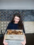 A menina guarda à disposição uma cesta com cones de abeto Fotos de Stock Royalty Free