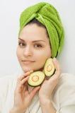 A menina guarda duas metades do abacate perto da cara Fotos de Stock Royalty Free