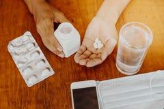 A menina guarda a medicina em sua mão com um vidro da máscara protetora da água e o telefone esperto em uma tabela de madeira Imagens de Stock