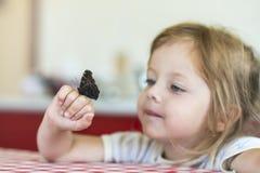 A menina guarda na mão a borboleta de Aglais io e olha-a para ele fotos de stock royalty free