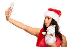 A menina guarda o boneco de neve que toma o selfie Imagens de Stock Royalty Free