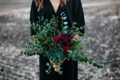 A menina guarda o ramalhete das flores e das hortaliças Imagem de Stock Royalty Free