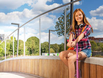A menina guarda o 'trotinette' ao sentar-se no lado de madeira Fotos de Stock