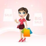 A menina guarda pacotes e mostra o dedo acima Foto de Stock Royalty Free