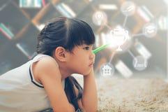 A menina guarda a pena em sua mão e pensa Educação e Fotos de Stock Royalty Free