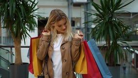 A menina guarda sacos de compras em seus ombros que estão na alameda video estoque