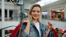 A menina guarda sacos de compras em seus ombros que estão em uma alameda video estoque