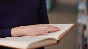 A menina guarda seus dedos nas páginas que lê um livro na biblioteca filme