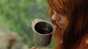 A menina guarda um copo do chá quente A menina bebe o chá na floresta video estoque