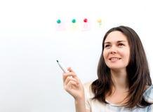 A menina guarda um marcador em uma mão em um fundo branco Imagem de Stock