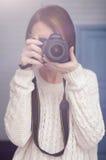 A menina guarda uma câmara digital e olha no visor ótico fotos de stock royalty free