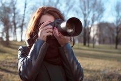 A menina guarda uma câmera em suas mãos e toma uma imagem imagens de stock