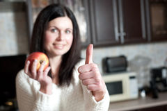 A menina guardara a maçã e mostra um polegar acima Foto de Stock