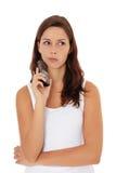 A menina hesita fazendo um atendimento de telefone Foto de Stock Royalty Free