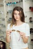 A menina hesita se precisa realmente pares de vidros novos Retrato da mulher à moda concentrada na compra, estando dentro fotografia de stock