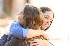 Menina hipócrita que abraça um amigo Imagens de Stock Royalty Free