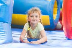 A menina idosa de cinco anos bagunçado está jogando no trampolim inflável grande Foto de Stock