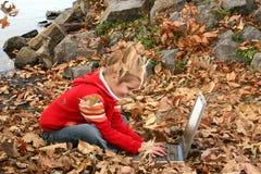 Menina idosa de cinco anos feliz que trabalha fora no portátil fotografia de stock royalty free