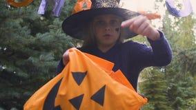 Menina impertinente em doces de exigência do traje da bruxa, jogo de Dia das Bruxas da doçura ou travessura vídeos de arquivo