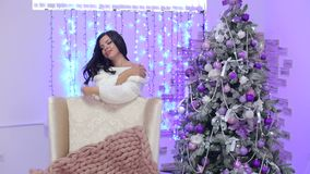 A menina inclinou-se na cadeira perto da árvore de Natal vídeos de arquivo