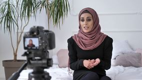 A menina indiana bonita nova no blogger do hijab que fala na câmera, contagens, insultou, gesticulando, a sala branca, conforto h vídeos de arquivo