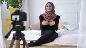 Menina indiana bonita nova no blogger do hijab que fala na câmera, gesticulando, sala branca, conforto home no fundo 50 filme
