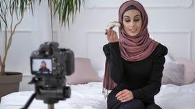 Menina indiana bonita nova no blogger do hijab que fala na câmera, sorrindo, falando na câmera, mostrando uma compra nova video estoque