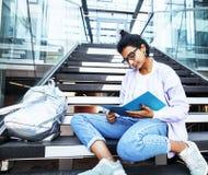 Menina indiana bonito nova na construção da universidade que senta-se em escadas Foto de Stock Royalty Free
