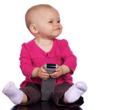 Menina infantil que joga com um telecontrole Imagens de Stock Royalty Free