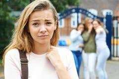 Menina infeliz que está sendo bisbilhotada aproximadamente por amigos da escola Fotografia de Stock