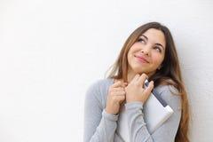 Menina inocente cândido do adolescente que afaga uma tabuleta e que olha acima Foto de Stock