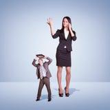 Menina irritada alta que fala no telefone, homem pequeno Fotografia de Stock Royalty Free