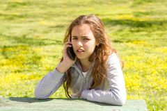 Menina irritada bonita do adolescente com o smartphone m?vel do cellpfone no parque do ver?o foto de stock
