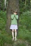 Menina irritada bonito pequena que está na árvore. fotografia de stock royalty free