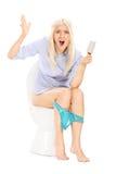 Menina irritada que guarda um rolo vazio do papel higiênico Imagens de Stock