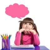 A menina isolada em uma camisa cor-de-rosa está sentando-se na sagacidade da tabela foto de stock