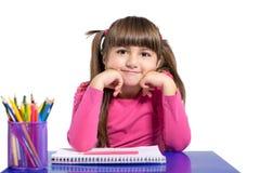 A menina isolada está sentando-se na tabela com lápis colorido foto de stock