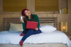 Menina japonesa asiática feliz bonita nova no chapéu do inverno relaxado no cartão de crédito da terra arrendada da cama usando o imagens de stock