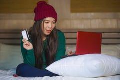 Menina japonesa asiática feliz bonita nova no chapéu do inverno relaxado no cartão de crédito da terra arrendada da cama usando o fotos de stock royalty free