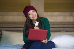 Menina japonesa asiática feliz bonita nova no chapéu do inverno relaxado no cartão de crédito da terra arrendada da cama usando o imagens de stock royalty free