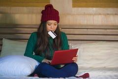 Menina japonesa asiática feliz bonita nova no chapéu do inverno relaxado no cartão de crédito da terra arrendada da cama usando o foto de stock