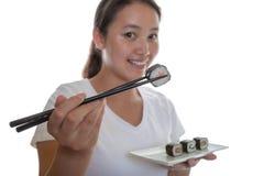 Menina japonesa que mostra o rolo de sushi com varas Imagem de Stock Royalty Free