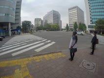 A menina japonesa típica da escola está cruzando a rua foto de stock