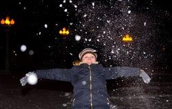 A menina joga acima uma braçada da neve Fotos de Stock Royalty Free