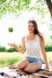 a menina joga acima uma maçã a menina bonita tem um resto no Fotos de Stock