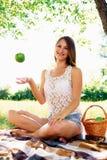 a menina joga acima uma maçã a menina bonita tem um resto no Foto de Stock
