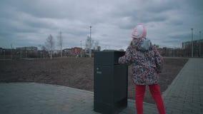 A menina joga a casca da banana no parque do maca-escaninho em público video estoque