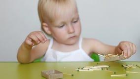 A menina joga com fósforos, arranja fósforos em uma caixa de fósforos, em um close-up, em um perigo, em umas crianças e em um fog filme