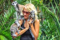 A menina joga com a família dos lêmures de Madagáscar Fotos de Stock Royalty Free